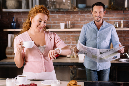 rigor: How many time do we have. Smiling middle-aged woman looking at her smartwatch and having coffee while her man reading a newspaper behind her Stock Photo