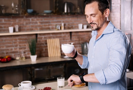rigor: What time is it. Smiling middle-aged man looking at his smartwatch while having coffee in the morning