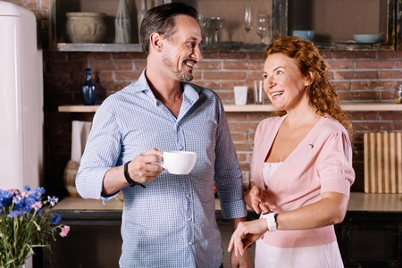 enquiring: We have to go. Demanding woman pointing on the watch and looking at her husband who holding a cup of coffee Stock Photo