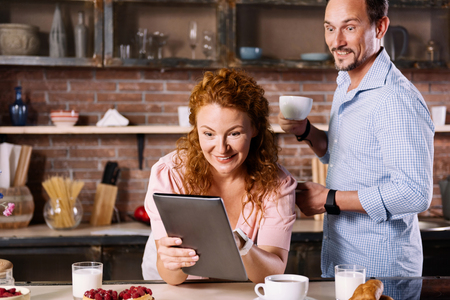 enquiring: It is cant be true. Surprised woman looking at the tablet and showing it to her husband who holding a cup and opening his eyes wide