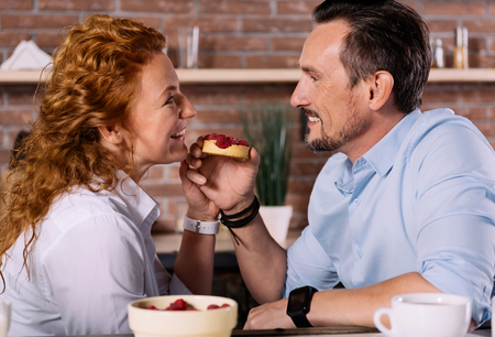 exciting: You have amazing eyes. Exciting man looking at eyes of his beautiful wife while feeding her with a cake