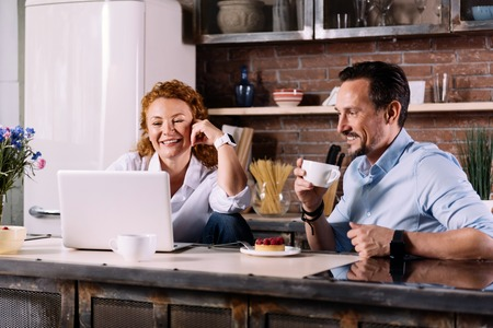 interested: Look here. Relaxed woman and interested man looking at the laptop while sitting at the table in the kitchen