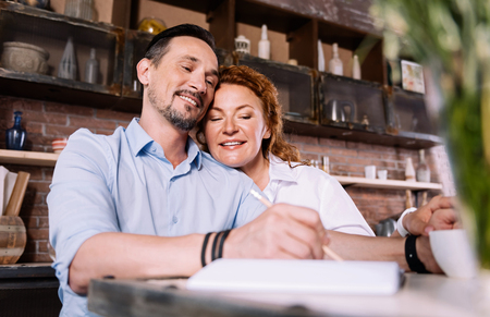 not forget: For not forget. Pleasant middle aged couple sitting in their kitchen and making a list of purchases Stock Photo