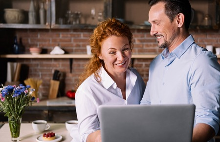 enquiring: It is funny. Cheerful woman laughing while looking at the laptop and standing near a man who smiling and looking at her in the kitchen