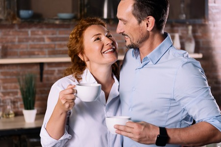 unforgettable: Unforgettable moment. Charming middle aged woman and a mature man looking at each other while holding cups of coffee