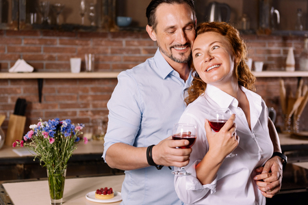 contented: You are my precious. Contented mature man hugging an energetic woman from the back while drinking wine in the kitchen