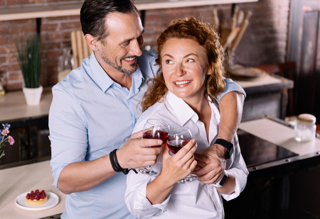 aged: Are you having a nice evening. Adorable middle aged couple cuddling and clanging glasses together while standing in the kitchen
