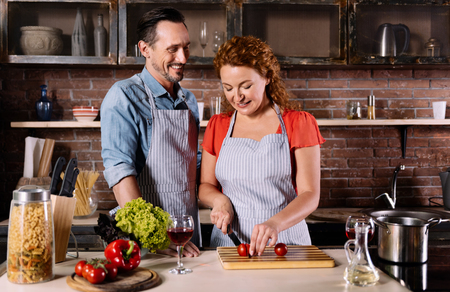 contented: Lets make something delicious. Contented mature man and energetic woman cutting vegetables for making a dinner Stock Photo