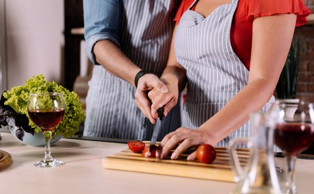 be careful: Be careful. Close up of hands of a man and a woman cutting tomatoes together in the kitchen Stock Photo