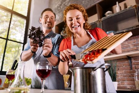 Lässt einen Gefallen hinzuzufügen. Lächelnde Frau, die einen Schnitt Gemüse zu einem Topf Zugabe, während sein Mann Basilika Beratung hinzufügen