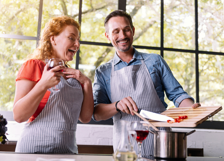Good job. Confident man adding vegetables to the pot while his wife admiring his work in the kitchen