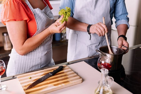 atmosphere: Smell so good. Close up of hands of man and woman cooking a delicious dish for a dinner Stock Photo