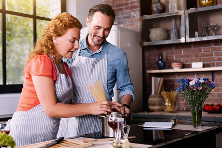 starving: I am starving. Good looking woman and bearded mature man cooking a pasta together in a stylish kitchen