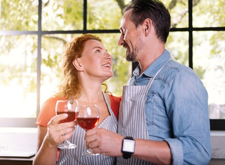 Unforgettable evening. Charming woman and handsome man looking at each other with love while clinking wine glasses in the kitchen Stock Photo