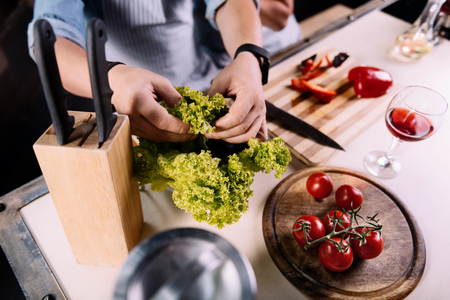 taking a wife: We need it. Close up of hands of a man taking leaves of salad while helping his wife to cook