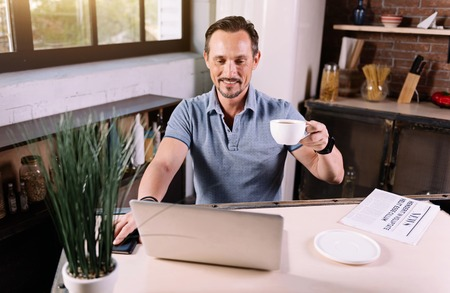 amiable: Lets look here. Pleasant amiable mature man using the laptop while sitting at the in the kitchen