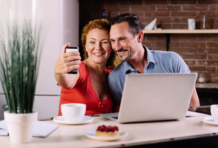 contented: Let me take a selfie. Contented mature man and an energetic woman taking a selfie while sitting at the table in their kitchen