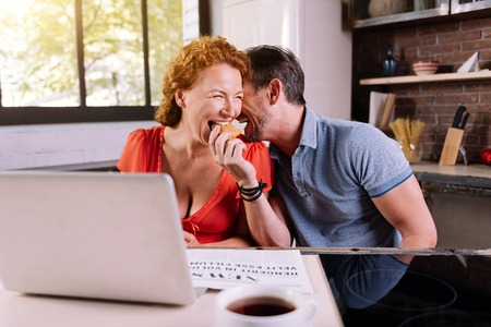 raspberry dress: So funny. Mature man giving a croissant to his charming wife while laughing together and having breakfast in their kitchen