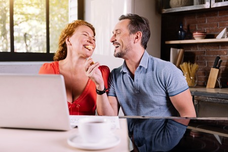 vibe: Eat it. Ecstatic man laughing at his wife eating a croissant while sitting at the table in the kitchen