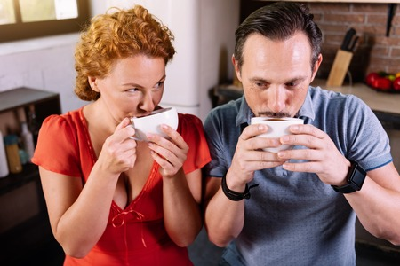 mouth couple: Funny morning. Cute middle aged couple drinking coffee and holding cups near mouth