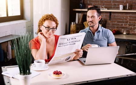 contented: Lets see. Contented middle aged woman reading a newspaper while her husband drinking coffee and talking to her in the kitchen Stock Photo