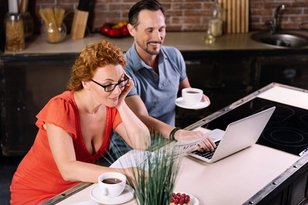 mid morning: Do you like morning. Charming middle aged woman with glasses reading a news while her husband using a laptop in the kitchen