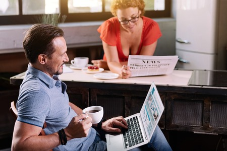 rigor: Know what is around you. Joyful mature bearded man sitting with the laptop and reading news while his wife with glasses reading a newspaper on the background Stock Photo
