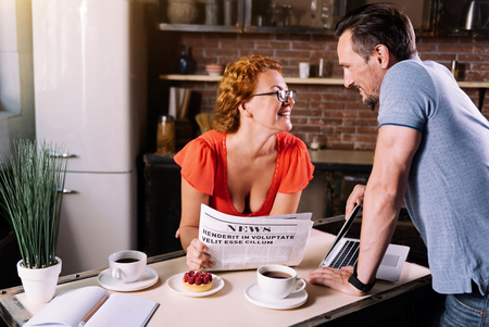 atmosphere: You are so beautiful today. Charming middle aged woman with glasses reclining on the table and reading news while her handsome mature man looking at her