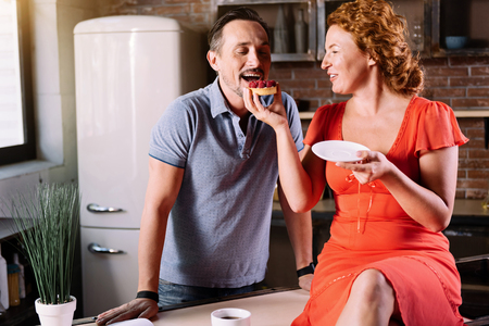 raspberry dress: Sweet as sugar. Exciting woman feeding her husband with a tasty cake while sitting on the table in dress and looking at him