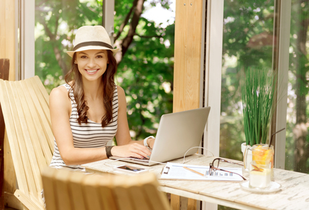 nomad: Feel the taste of every day. Cheerful delighted smiling woman sitting at the table and expressing joy while using laptop
