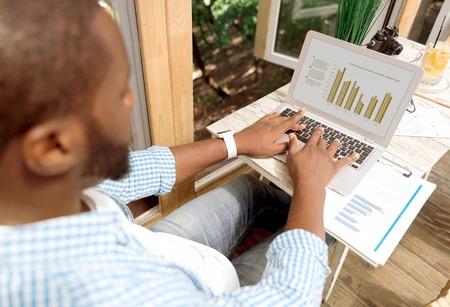 diligente: mente analítica. hombre diligente agradable sentarse en la mesa y trabajar en la computadora portátil mientras que la participación en el trabajo