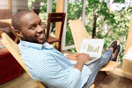 양성 공유. 자에 앉아 집에서 작업하는 동안 랩톱을 사용하는 쾌활한 기쁘게 미소 짓는 남자