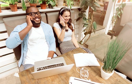 Get in touch. Cheerful delighted smiling colleagues sitting at the table and talking on phones while expressing joy
