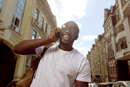 overjoyed: Joyful talk. Overjoyed delighted smiling man talking on cellphone while walking along the street Stock Photo