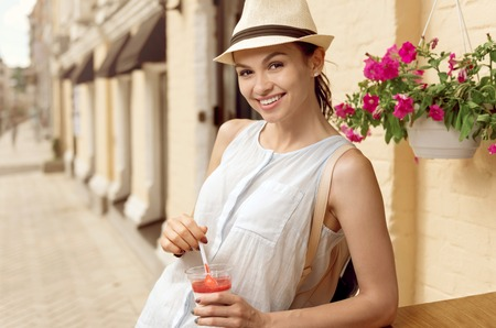 Refresh yourself. Cheerful young beautiful woman smiling and eating panna cotta
