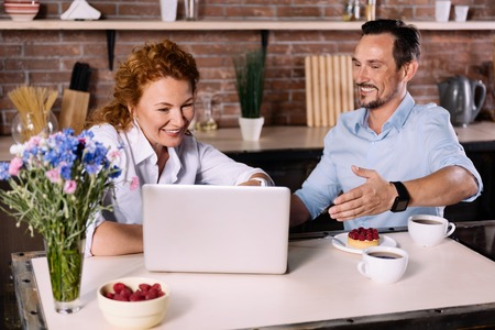 enquiring: Look how cool it is. Smiling woman looking at the laptop while the man making a sign with a hand toward the screen Stock Photo
