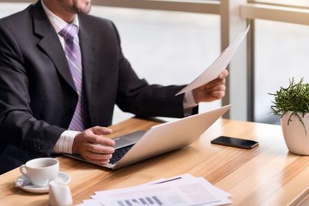 diligente: trabajador diligente. Agradable ocupado hombre de negocios señor sentado en la mesa y la celebración de los documentos mientras se trabaja