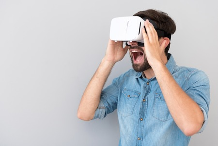 overjoyed: Great effect. Overjoyed delighted bearded man opening his mouth and expressing emotions while using virtual reality device