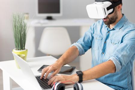 Chwytający moment. Zaangażowany przystojny mężczyzna siedzi przy stole i grając w gry komputerowe podczas noszenia okularów wirtualnej rzeczywistości