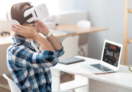 overjoyed: Feel the beat. Overjoyed delighted man sitting at the table and listening to music while using virtual reality glasses Stock Photo