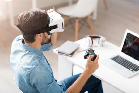 jugando videojuegos: Al igual que lo hace. simp�tico joven que se sienta en la silla y con gafas de realidad virtual en los videojuegos