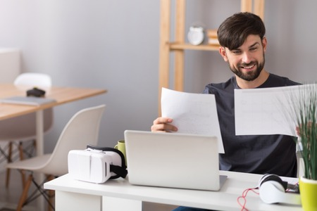 work addicted: Addicted to work. Positive content man sitting at the table and working with papers in the office while expressing joy