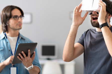 testing vision: New vision. Positive emotional man wearing virtual reality glasses while testing them with his colleagues while working in the office