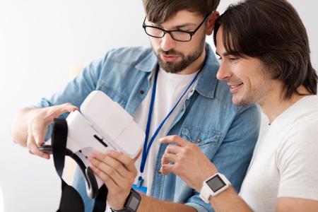 diligente: Mira aqu�. colegas diligentes positivos que sostienen unas gafas de realidad virtual mientras trabajan juntos