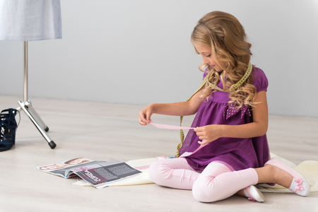 I need more pink ribbon. Pretty little girl sitting on the floor with a measuring tape on the neck and looking at the ribbon Stock Photo