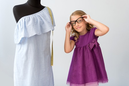 enchanting: To see you better. Enchanting little girl putting on glasses and looking at the camera while standing near a mannequin with a dress on it