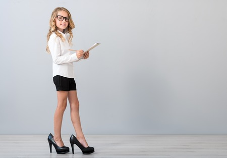 As a real adult. Smiling confident little girl wearing glasses and high heels and looking at the camera while standing with a pencil and writing in the notebooks