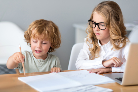 prudent: Show me. Prudent little girl with glasses looking at little adorable boy holding a pencil and drawing while sitting at the table Stock Photo