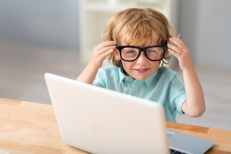 Is it fit me. Cute little boy touching glasses and looking at the camera while sitting at the table in front of a laptop Stock Photo