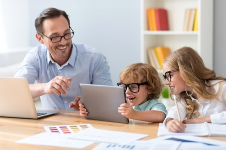 It is amazing. Smiling man and lovely children with glasses looking with interest at the tablet while sitting at the table